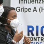 A woman and a man wearing masks to prevent infection from swine flu arrive at  the Miguel Couto hospital in Rio de Janeiro, Friday, July 24, 2009. (AP Photo/Ricardo Moraes)
