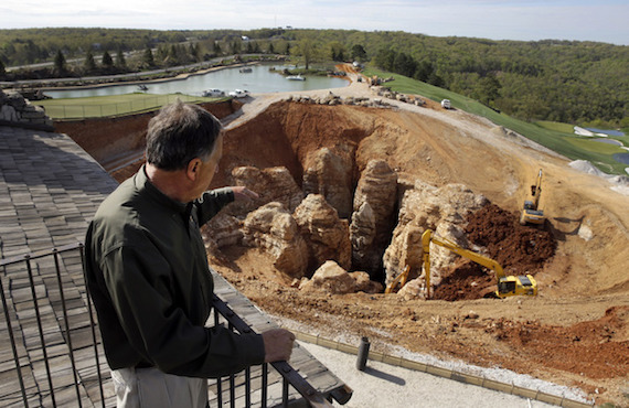 In this photo made Thursday, April 14, 2016, Johnny Morris, founder of Bass Pro Shops, points to a massive sinkhole that opened up on his golf course during heavy rain last spring in Ridgedale, Mo. Experts urged Morris to fill the hole with clay and boulders, but he was intrigued by the possibility that an unknown cave system was at the root of the sinkhole which he believes could tie into other caves nearby including one he himself discovered over two decades ago. (AP Photo/Jeff Roberson)