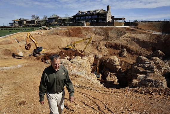 In this photo made Thursday, April 14, 2016, Johnny Morris, founder of Bass Pro Shops, walks around the edge of a massive sinkhole that opened up last spring on his golf course in Ridgedale, Mo. Morris, a cave enthusiast for years, believes the sinkhole and a cave he discovered about a half-mile away in 1993 are connected after water from a pond on the golf course drained into the hole and began pouring out the entrance to the cave. (AP Photo/Jeff Roberson)